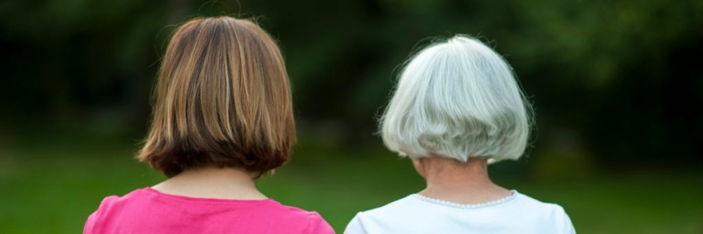 anonymous senior mother and mature daughter rear view