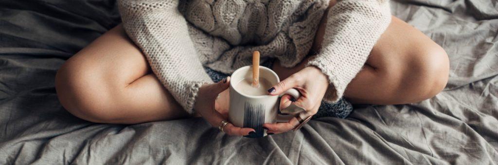 Caucasian woman enjoying a mug of hot coffee in the morning.