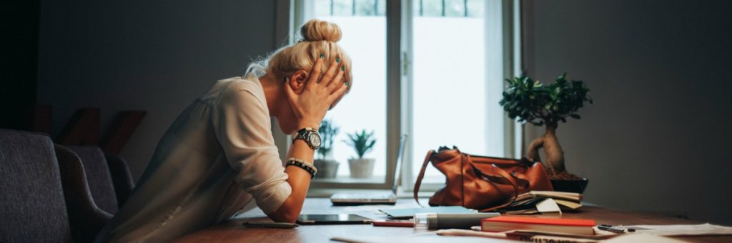 Tough day at work: businesswoman having a splitting headache.